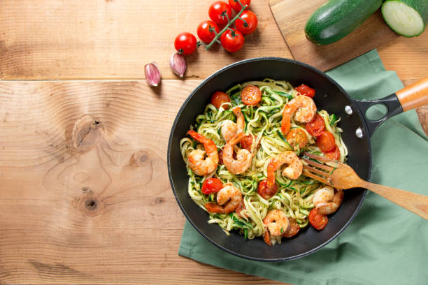 Zucchini noodles with cherry tomato and prawns in a pan stock photo