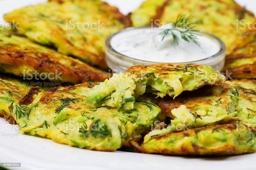 Zucchini Pancakes With  Sour Cream in White Plate. stock photo