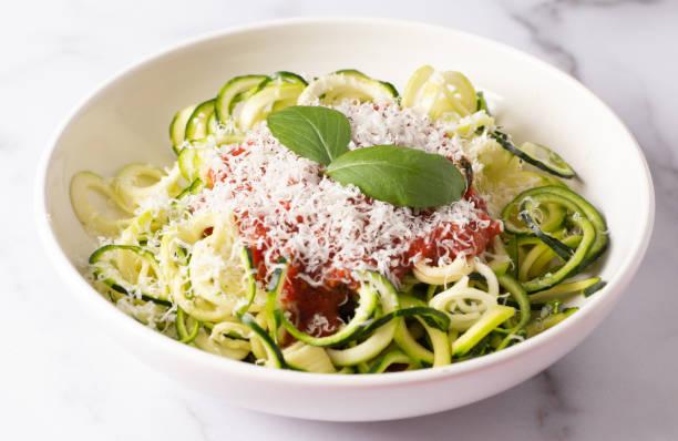 courgette pasta gegarneerd met parmesean kaas en tomatensaus - courgette stockfoto's en -beelden