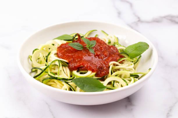 zucchini-pasta mit tomatensauce und basilikum garniert - gefüllte zucchini vegetarisch stock-fotos und bilder