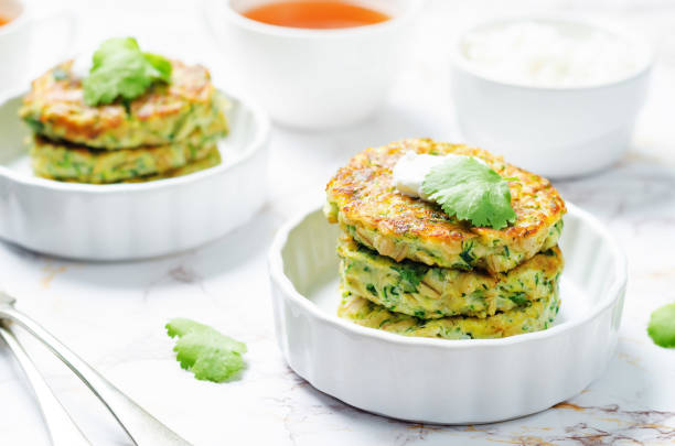 Zucchini ricotta cilantro fritters with fresh cilantro leaves Zucchini ricotta cilantro fritters with fresh cilantro leaves. toning. selective focus fritter stock pictures, royalty-free photos & images