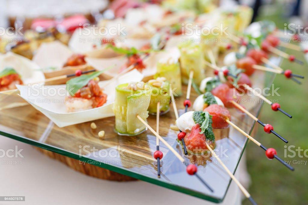 Zucchini Röllchen mit Pinienkernen. Cherry-Tomaten, Mozzarella und Basilikum auf Spieße stecken. . Pesto-Soße. Leckere Buffet-Tisch. Sommer-Party im Freien. – Foto