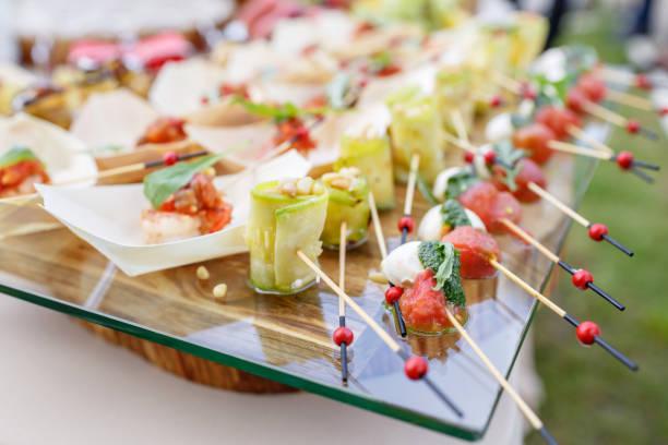 zucchini röllchen mit pinienkernen. cherry-tomaten, mozzarella und basilikum auf spieße stecken. . pesto-soße. leckere buffet-tisch. sommer-party im freien. - caprese salat stock-fotos und bilder