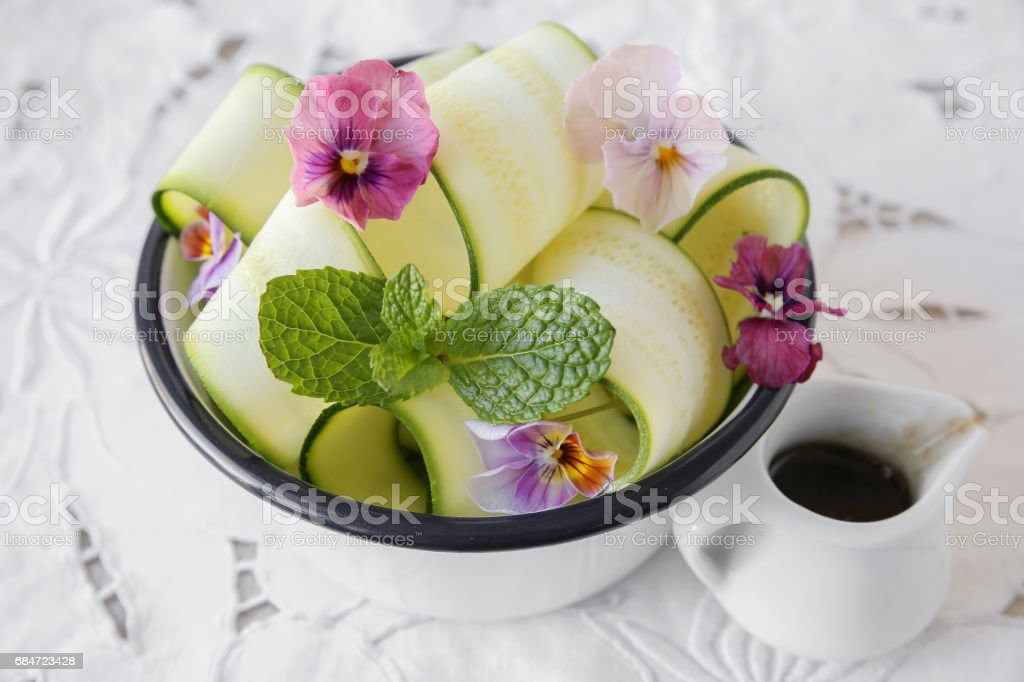 Zucchini salad with edible flowers, summer vegan salad stock photo