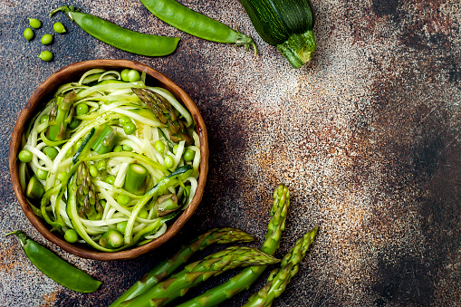 istock Zucchini spaghetti or noodles (zoodles) bowl with green veggies. Top view, overhead 827947128