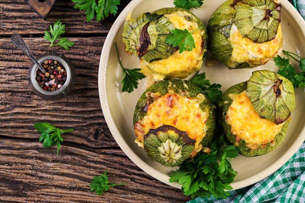 zucchini gefüllt mit hackfleisch, käse und grünen kräutern. im ofen gebacken. ansicht von oben - gefüllte zucchini vegetarisch stock-fotos und bilder