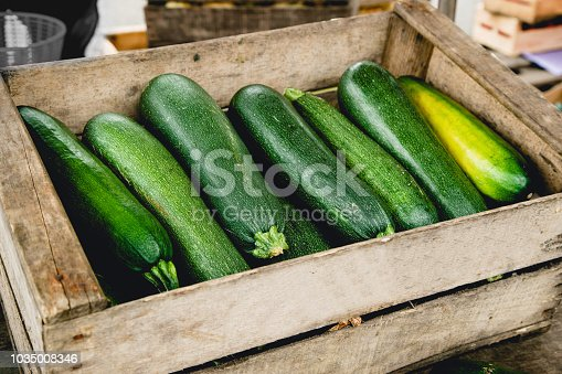 Zucchinis in wooden box at the market