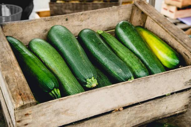 courgettes in houten doos op de markt - courgette stockfoto's en -beelden