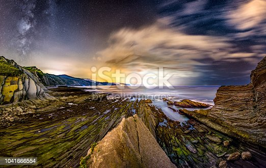 Panoramic view of Zumaia flysh at night with clouds and milky way