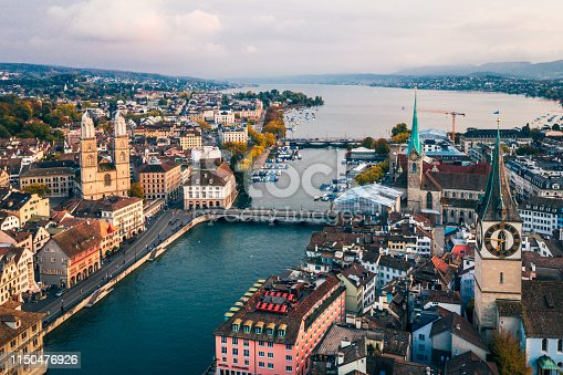 Aerial view of Zurich, Switzerland. Taken from a drone overlooking the Limmat River. Beautiful blue sky with dramatic cloudscape over the city. Visible are many traditional Swiss houses, bridges and churches.