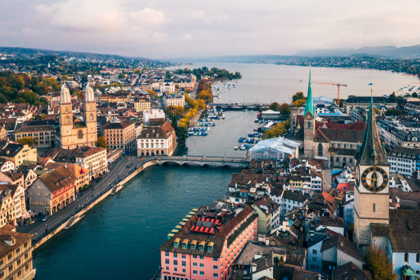Zurich aerial view Aerial view of Zurich, Switzerland. Taken from a drone overlooking the Limmat River. Beautiful blue sky with dramatic cloudscape over the city. Visible are many traditional Swiss houses, bridges and churches. fraumunster stock pictures, royalty-free photos & images