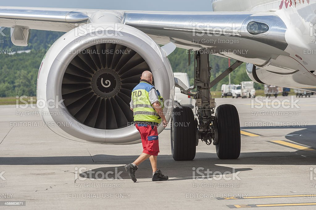 Zurich airport ground crew mechanic passing by Boeing 737 engine stock photo
