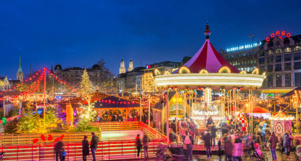 Zurich Christmas Market at Bellevue and Sechseläutenplatz Panoramic view over Zurich´s Christmas Market at the recently reconstructed public town squares Bellevue / Secheseläutenplatz right in front of the Opera house and next to the Zurich lake with the landmark Grossmunster cathedral in the distance. zurich stock pictures, royalty-free photos & images