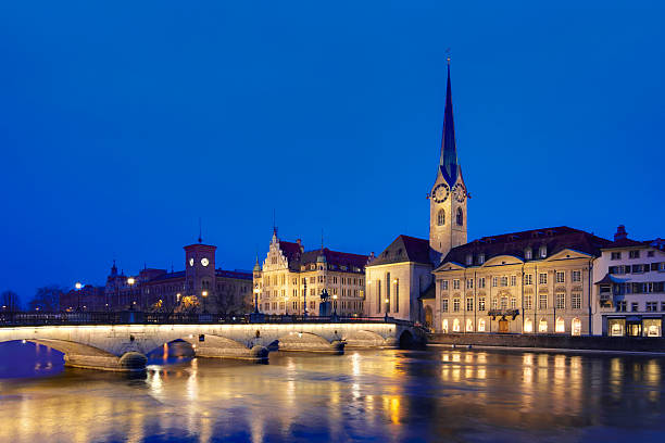 Zurich, Fraumünster church at the dusk Dusk panoramic view onto the church and clocktower in the heart of Zurich historical center fraumunster stock pictures, royalty-free photos & images