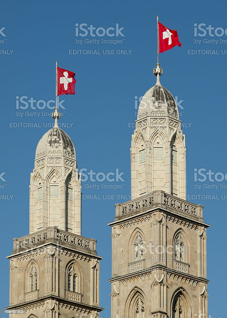 Zurich Grossmunster church towers with Swiss flags stock photo