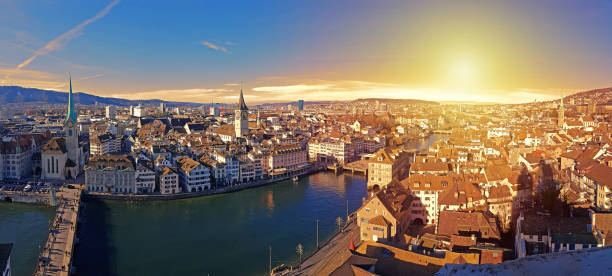 Zurich in sunset panorama with river Limmat Panoramic view of Zurich city in sunset and river Limmat, Switzerland. zurich stock pictures, royalty-free photos & images