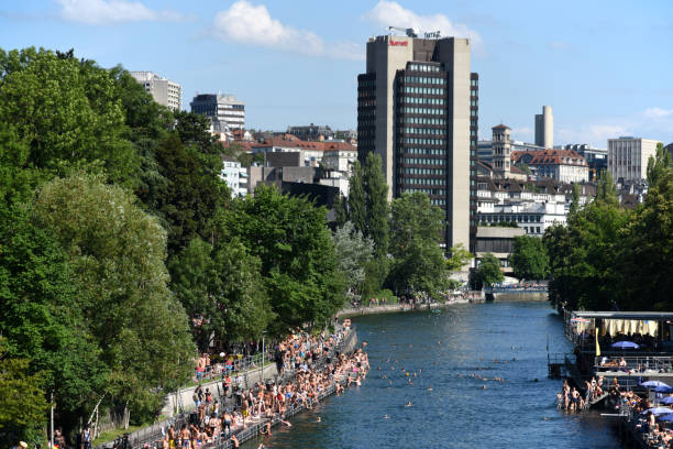 Zurich Limmat with swimming people The River Limmat with people takimng a sunbath and swimming on a sunny day. limmat river stock pictures, royalty-free photos & images