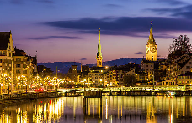 Zurich on banks of Limmat river on a winter evening Zurich on banks of Limmat river on a winter evening limmat river stock pictures, royalty-free photos & images