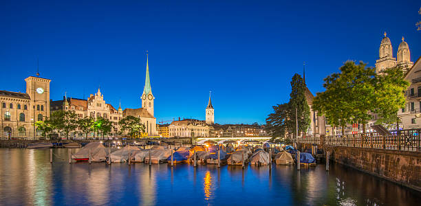 Zurich panorama at dusk Zurich skyline and boats on the Limmat river at dusk limmat river stock pictures, royalty-free photos & images