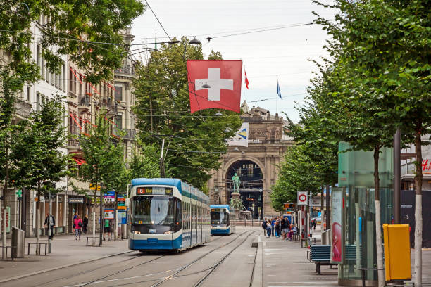 Zurich shopping street Bahnhofstrasse with tram and swiss flag Zurich, Switzerland - June 10, 2017: Shopping promenade called Bahnhofstrasse, inner city of Zurich. Tram / train with swiss flag in front. zurich stock pictures, royalty-free photos & images