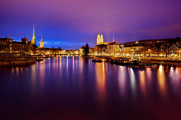 Zurich skyline and the Limmat river at night view on Fraumunster Church, Church of St. Peter and Grossmunster at night, Zurich, Switzerland fraumunster stock pictures, royalty-free photos & images