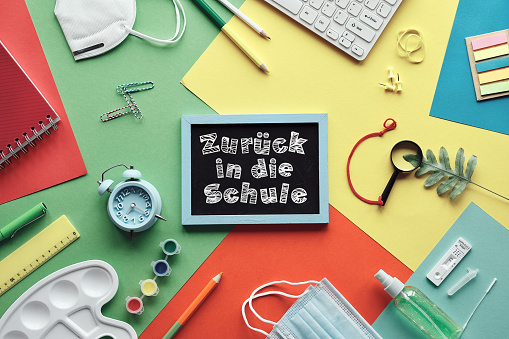 Zuruch in die Schule means or back to school in German language. Concept top view with chalk text on blackboard. Corona quick tests, mask, stationary. Flat lay on layered colored paper background