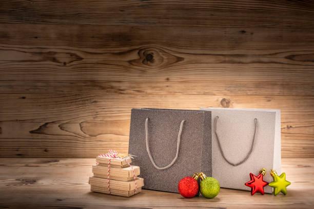 zwei einkaufstaschen mit geschenke und weihnachtsdekoration - engelsflügel kaufen stock-fotos und bilder