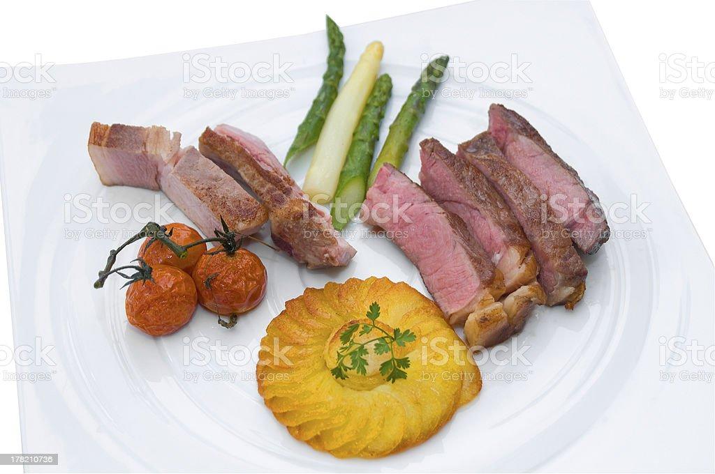 Zweierlei Fleisch mit Beilagen auf weissem Teller stock photo