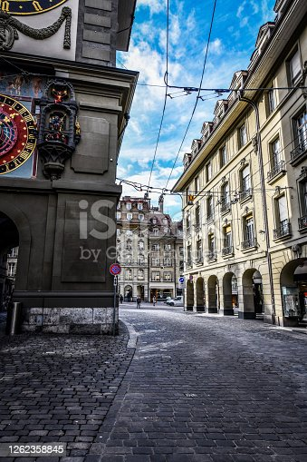The center of Bern near the Zytglogge clocktower architectural arch passage and cobbled streets. On the rights side there are marketplaces and on the left side is the clocktower itself.