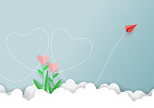 Paper art style of valentine's day greeting card and love concept.Red paper airplane flying above love plants on clouds and blue sky.Vector illustration.