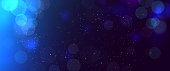 Abstract blurred bokeh blue background with circles. Christmas and New year holiday magic background with snow. Copy space