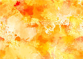 An abstract watercolour autumn background with yellow and orange brush strokes and splashes of paint