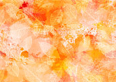 An abstract watercolour autumn background with yellow and orange brush strokes and splashes of paint, and leaf silhouettes