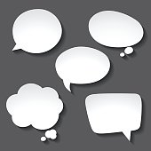 Abstract white paper speech bubbles on gray background.