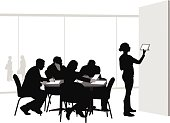 A vector silhouette illustration of a woman giving a presentation at a business meeting. She uses a tablet to illustrate points to business men and woman sitting and taking notes.