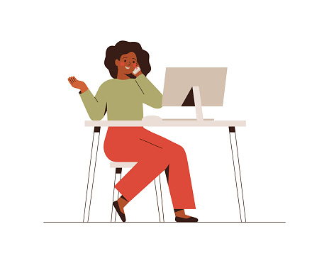 African American female is talking phone and looking at the computer. Business woman or freelancer works at home or office.