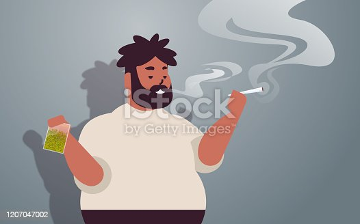 istock african american guy smoking cannabis joint fat rastaman holding green dry crushed marijuana leaves in plastic bag drug consumption concept portrait horizontal 1207047002