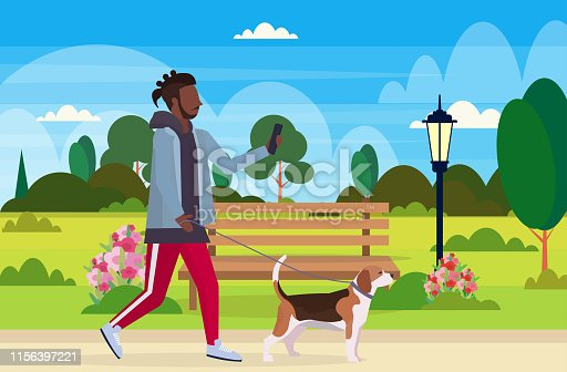 istock african american man walking with dog using smartphone social media network communication digital gadget addiction concept city urban park landscape background flat full length horizontal 1156397221