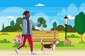 istock african american man walking with dog using smartphone social media network communication digital gadget addiction concept city urban park landscape background flat full length horizontal 1156397221
