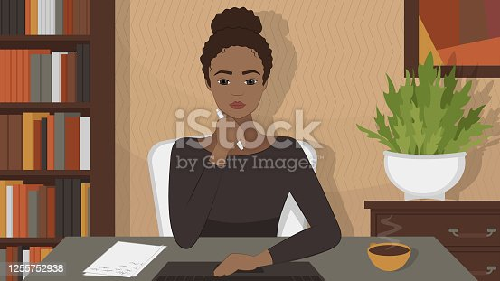 istock African American woman sits at desk and looks at the monitor. A young woman watches an online training webinar and takes notes. Remote work, study from home. 1255752938