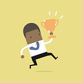 African businessman jumping and holding trophy.