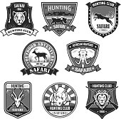 African safari animal hunting club and outdoor adventure badge set. African elephant, lion, rhino, antelope, panther, leopard with rifle and savanna landscape on heraldic shield with ribbon banner