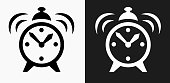 Alarm Clock Icon on Black and White Vector Backgrounds. This vector illustration includes two variations of the icon one in black on a light background on the left and another version in white on a dark background positioned on the right. The vector icon is simple yet elegant and can be used in a variety of ways including website or mobile application icon. This royalty free image is 100% vector based and all design elements can be scaled to any size.