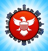 American Eagle and Shield  on Rural Cityscape Skyline Background. The button is in the center of the illustration. a detailed 100% vector rural cityscape skyline is placed around the circumference of the button and includes various houses, single family homes, residential condominium and other suburb buildings. There is a blue sky background with a star burst glow rendered behind the buildings. The image is ideal for displaying rural suburban life concepts and ideas.