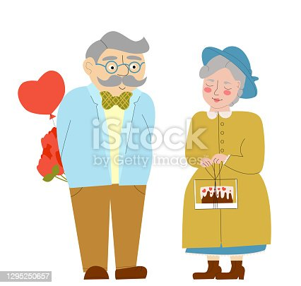 istock An elderly couple gives each other gifts. 1295250657