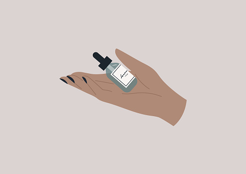 An elegant hand holding a bottle of beauty serum, skin care daily routine