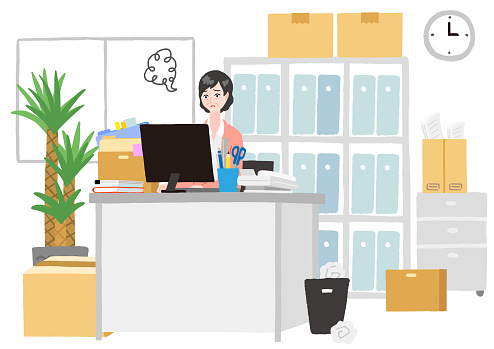 An older woman working in a cluttered office