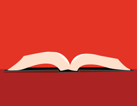 An opened white pages book on a red surface