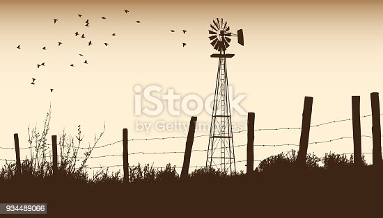 Vintage rural scenery with windmill and barbwire fence in sepia tone