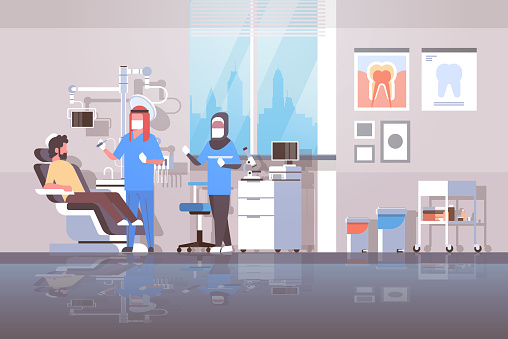 arab dentist with assistant in hijab drilling teeth of man patient lying in dentistry chair professional dental office modern clinic interior arabic characters full length flat horizontal